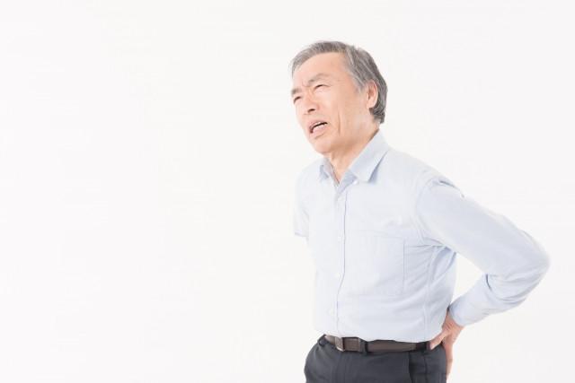 腰を抑える男性の写真